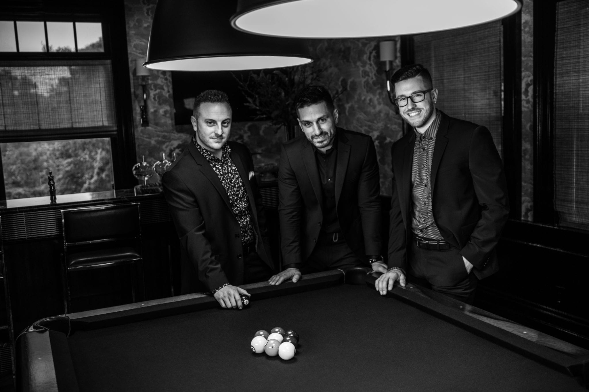 Three men standing by a pool table in suits.