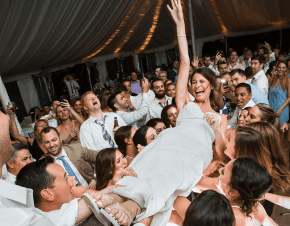 A bride being carried by her guests at her wedding | Elegant Music Group - EMG