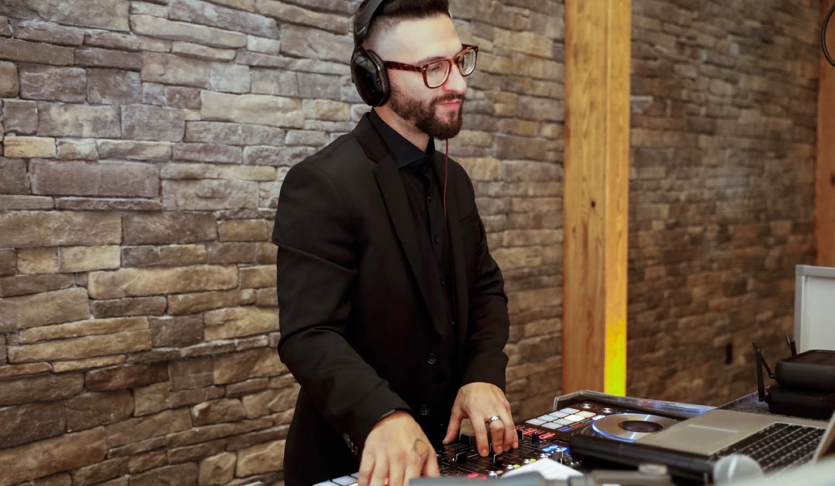 A DJ with headphones on in front of a brick wall.