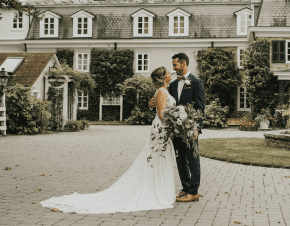 A bride and a groom sharing a loving look in front of a beautiful wedding venue | Elegant Music Group - EMG