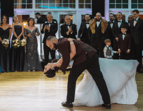A groom dipping his bride while they dance in front of their guests | Elegant Music Group - EMG