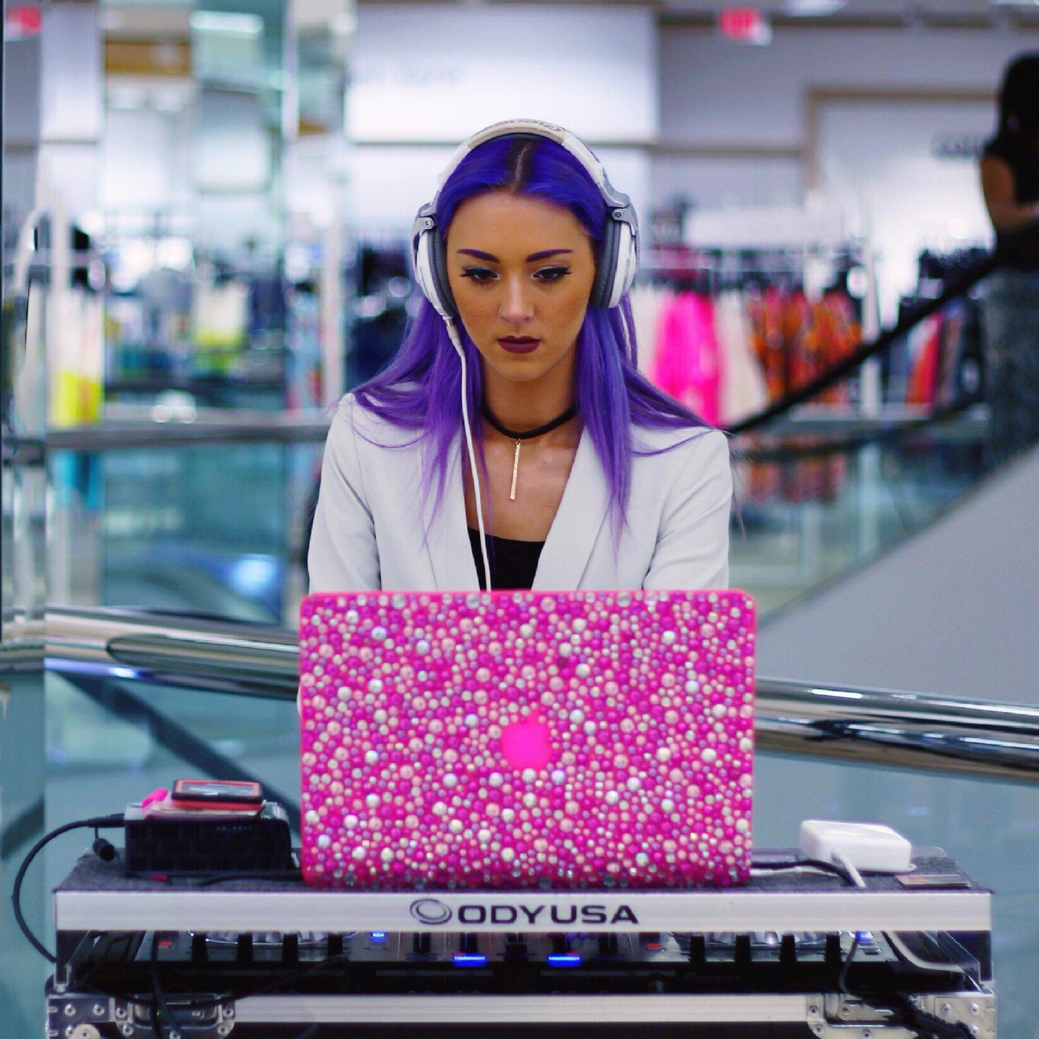 DJ Chelli at a pink laptop.